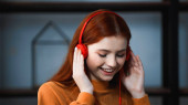 Smiling red haired girl using headphones at home