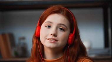 Smiling girl in headphones looking at camera at home