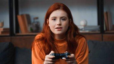 KYIV, UKRAINE - NOVEMBER 8, 2019: Smiling girl playing video game at home stock vector