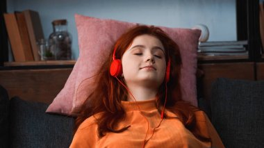 Girl in headphones relaxing on pillows at home