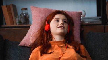 Smiling girl listening music in headphones on pillows