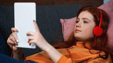 Teenager in headphones using digital tablet on blurred foreground