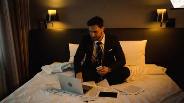 Businessman in earphones using laptop while holding smartphone near papers on hotel bed