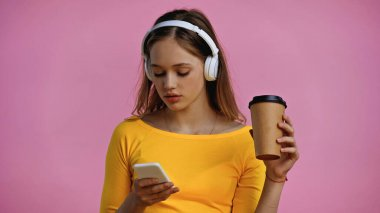 teenage girl in wireless headphones using smartphone and holding paper cup isolated on pink