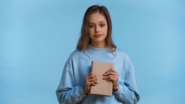 Teenage girl in sweatshirt holding book while looking at camera isolated on blue stock vector
