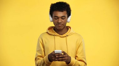 african american teenage boy in wireless headphones using smartphone isolated on yellow