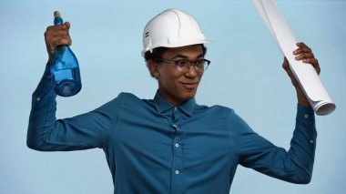 African american teenage boy in hard hat holding paper roll and bottle with champagne isolated on blue stock vector
