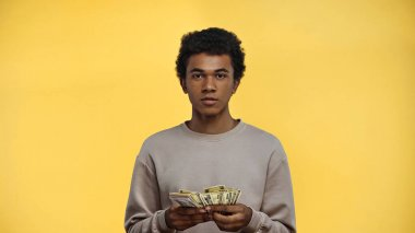 African american teenage boy in sweatshirt holding dollars isolated on yellow stock vector
