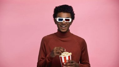 Happy african american teenager in 3d glasses holding popcorn bucket isolated on pink stock vector