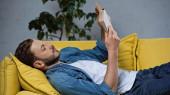 vousatý muž ležící na pohovce a čtení knihy v obývacím pokoji