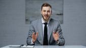 Geschäftsmann im Anzug redet, während er im Büro gestikuliert
