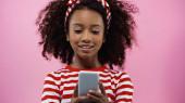 glücklich afrikanisch amerikanische Mädchen SMS auf Smartphone isoliert auf rosa