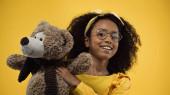 boldog afro-amerikai lány szemüvegben tartja Teddy maci elszigetelt sárga