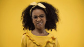 curly african american girl in glasses sticking out tongue isolated on yellow