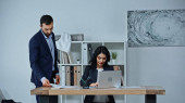 Businessman holding document near colleague using laptop in office