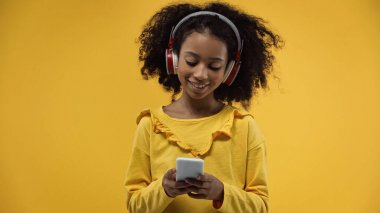 curly african american girl in headphones using smartphone isolated on yellow