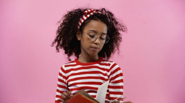 Curly african american girl in glasses reading novel isolated on pink stock vector