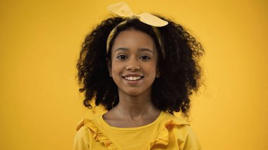 Happy and curly african american girl looking at camera isolated on yellow stock vector