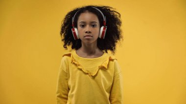 curly african american girl in wireless headphones isolated on yellow