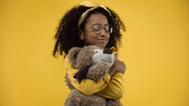 Curly african american girl in glasses hugging teddy bear isolated on yellow stock vector