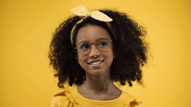 Dreamy african american girl in glasses looking away and smiling isolated on yellow stock vector