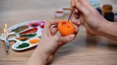 oříznutý pohled na ženu malování oranžové velikonoční vejce