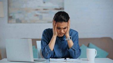 Nervous freelancer touching head near laptop on desk stock vector