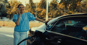 Glückliche Frau beim Tanken von Auto an Tankstelle am Smartphone