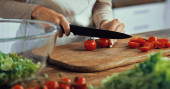 cropped view of woman cutting cherry tomatoes on chopping board