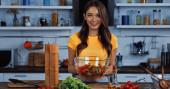 veselá žena drží misku s čerstvým míchaným salátem