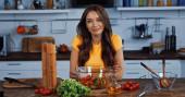 vidám fiatal nő mosolygós közelében tál friss vegyes saláta