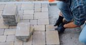 oříznutý pohled na člověka pracujícího s dlaždicovými kameny na staveništi