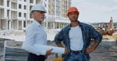 zralé inženýr s plány mluvit s stavitelem na staveništi