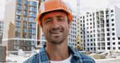 Hezký stavitel se usmívá na kameru na staveništi