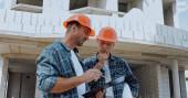 Stavitelé se dívají na schránku a mluví na staveništi