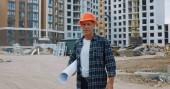 stavitel středního věku, držící plán a stojící na staveništi