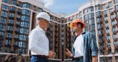 nízkoúhlý pohled inženýra a stavitele mluvícího v blízkosti nové budovy