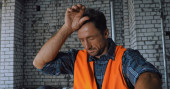 Tired builder touching forehead on construction site