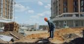 středního věku stavitel v pevném klobouku kopání země s lopatou na staveništi