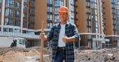 Usmívající se stavitel drží lopatu a ukazuje palec nahoru na staveništi