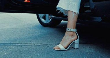 Moda ayakkabılı bir kadının arabadan inişi.