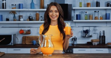 Cheerful young woman holding jug with orange juice and glass stock vector