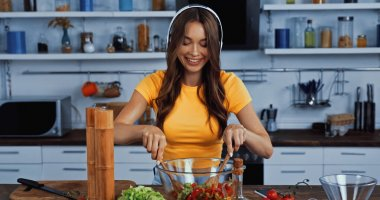happy woman in wireless headphones listening music and mixing salad
