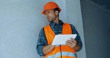 Builder in safety helmet holding digital tablet on construction site stock vector