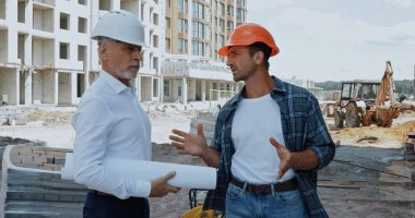 Engineer with blueprints talking with builder in hard hat on construction site stock vector