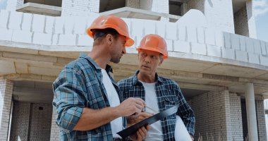 Builders looking at each other and talking on construction site stock vector
