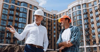Low angle view of engineer gesturing near builder while talking near new building stock vector