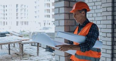 Pensive builder in helmet looking at blueprint on construction site stock vector