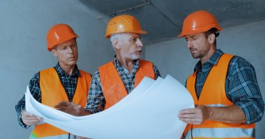 Builders in safety helmets talking while holding blueprints on construction site stock vector
