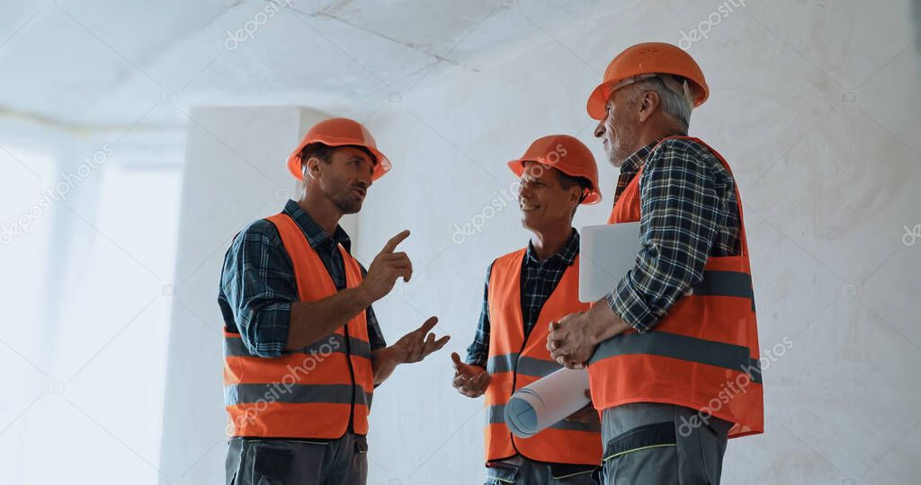 Builder gesturing while talking with coworkers on construction site stock vector